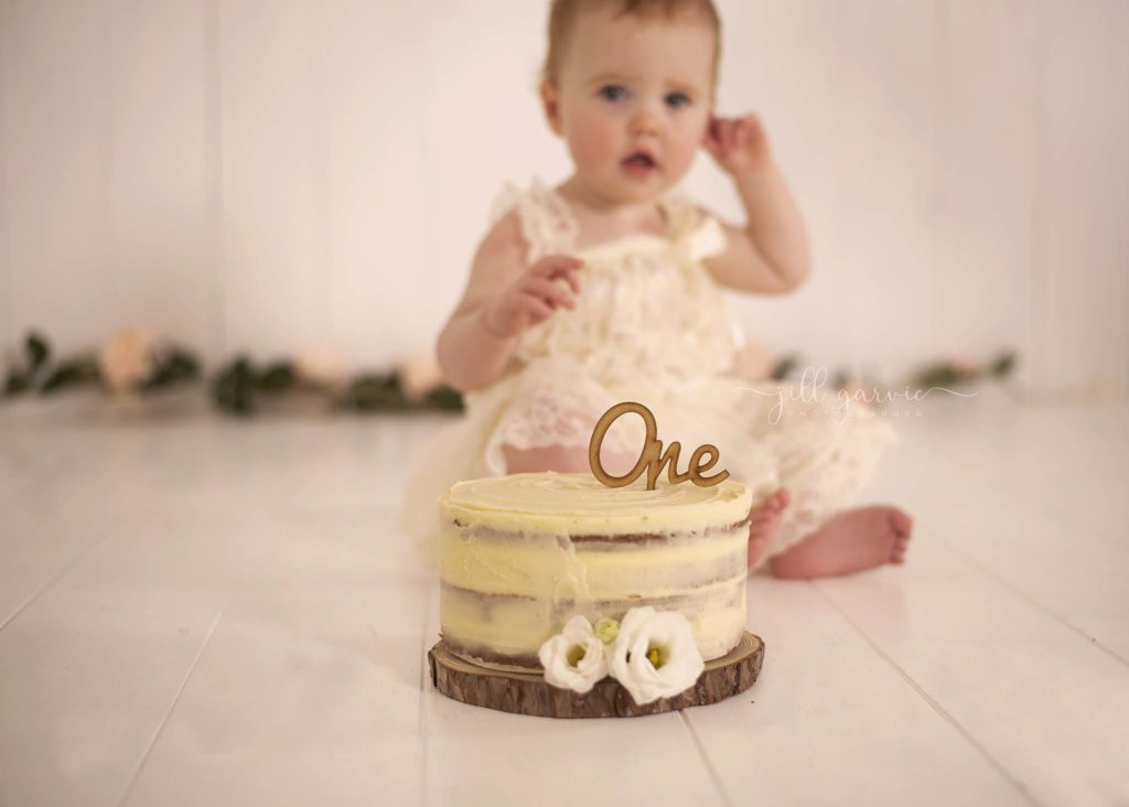 Photograph of Baby girl at first birthday cake smash taken at Jill Garvie Photography studio in Edinburgh